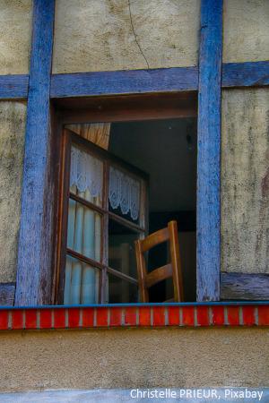 Hauswand mit offenem Fenster, dahinter steht ein leerer Holzstuhl.